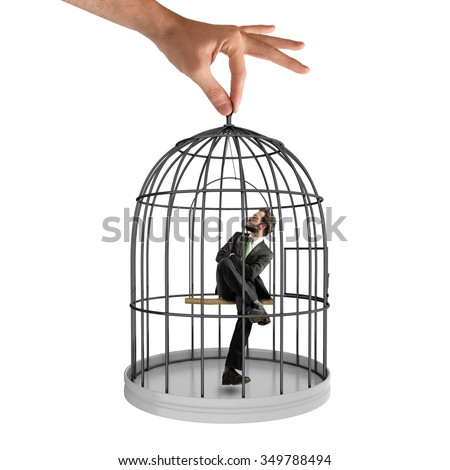 Businessman sitting in a cage of birds - stock photo