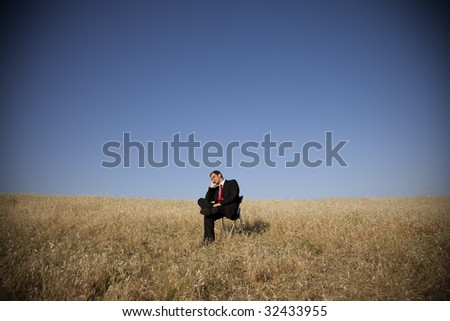 businessman sitting in a chair in outdoor looking to the field (intentional vignetting)