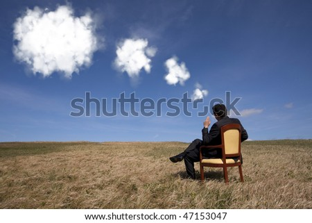 businessman sitting in a chair thinking about the future the field - stock photo