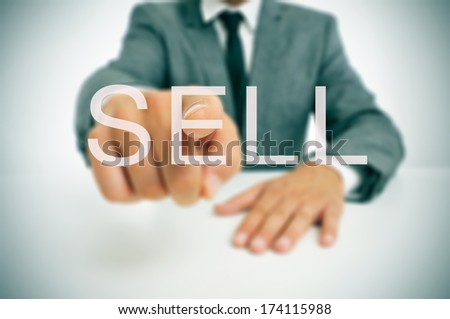 businessman sitting in a desk pointing the word sell written in the foreground - stock photo
