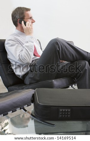 Businessman sitting in a lounge and talking on cell phone