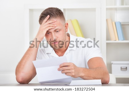 Businessman sitting in an office reacting in shock to the contents of a letter that he is reading raising his hand to his mouth - stock photo
