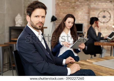 Businessman sitting in busy office, looking at camera. - stock photo