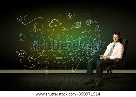 Businessman sitting in chair holding tablet with media icons concept on background