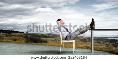 Businessman sitting in chair with legs on table and relaxing - stock photo