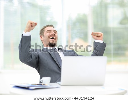 Businessman sitting in front of his open laptop with his fists raised in the air and a beaming smile of success - stock photo