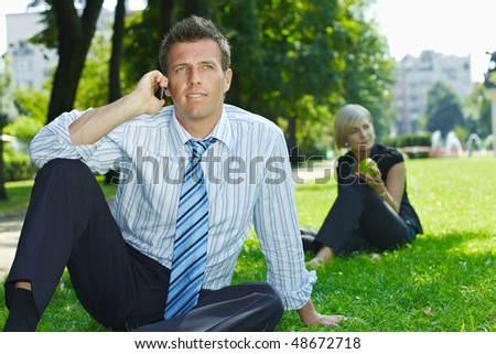 Businessman sitting in grass in park, talking on mobile. Busineswoman relaxing in the background. - stock photo