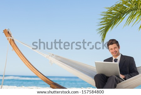 Businessman sitting in hammock using laptop looking at camera on beach - stock photo