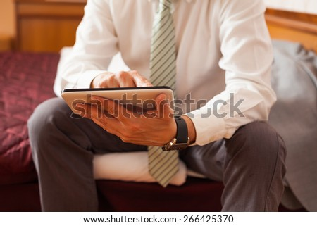 Businessman sitting in hotel room and using tablet computer - stock photo
