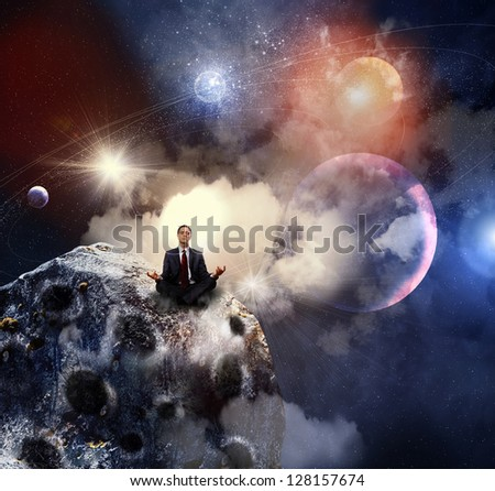 Businessman sitting in lotus flower position against space background - stock photo