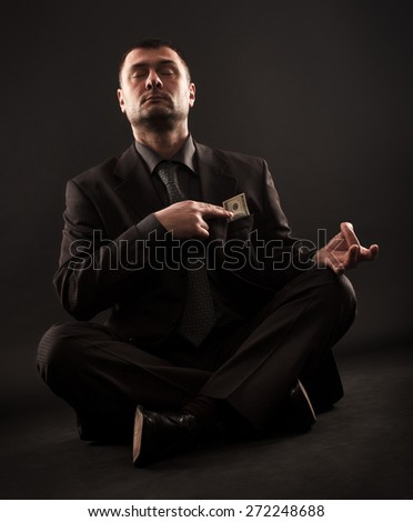 Businessman sitting in lotus position doing yoga and holding one hundred dollar bill on his heart with right hand. - stock photo