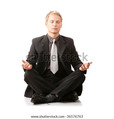 Businessman sitting in lotus position isolated