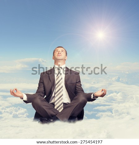 Businessman sitting in lotus position on cloud and looking up