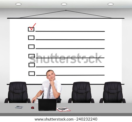 businessman sitting in office and drawing check box on poster - stock photo