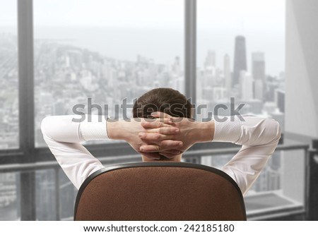 Businessman sitting in office and looking in city - stock photo