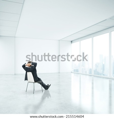 Businessman sitting in office and looking through window