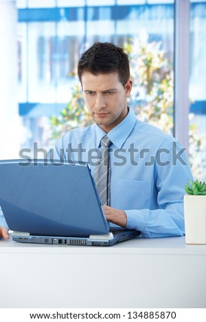 Businessman sitting in office, concentrating on working on laptop computer.