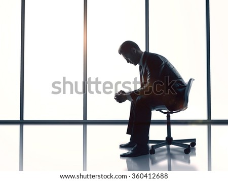 businessman sitting in office on chart and thinking - stock photo