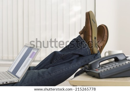 Businessman sitting in office with feet up on desk, using laptop in lap, side view, low section - stock photo