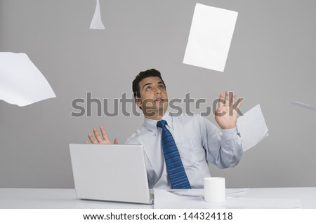 Businessman sitting in office with papers falling around him - stock photo