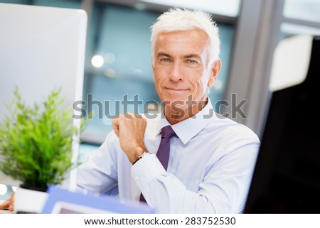 Businessman sitting in office working with computer - stock photo