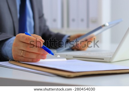Businessman sitting in office, working with laptop computer . - stock photo