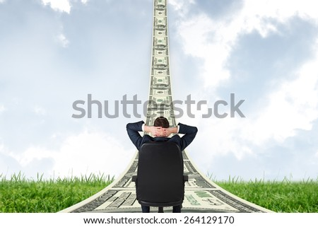 Businessman sitting in swivel chair against field and sky - stock photo