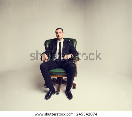 Businessman sitting in the big chair. Manager, Boss. Think about work, business, transactions, money, profit, revenue, graphics deal. To reflect on the issues of work and production. Business attire.