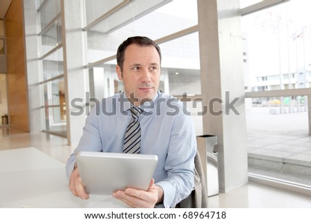 Businessman sitting in the office with electronic tablet - stock photo