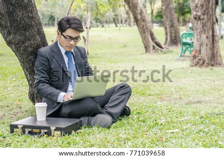Businessman sitting in the park and having fun with laptop and coffee.