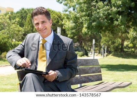 Businessman sitting in the park outdoors with a tablet