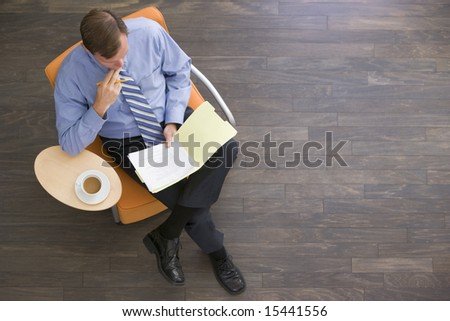Businessman sitting indoors with coffee and folder - stock photo