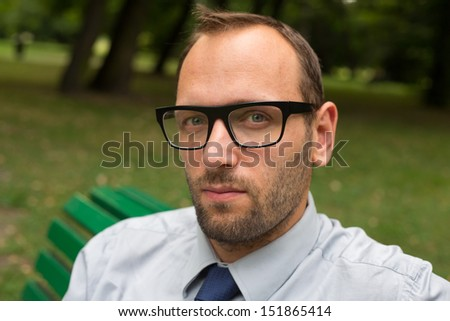 Businessman sitting on a bench in the park.
