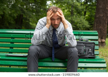 Businessman sitting on a bench with headache in the park. - stock photo