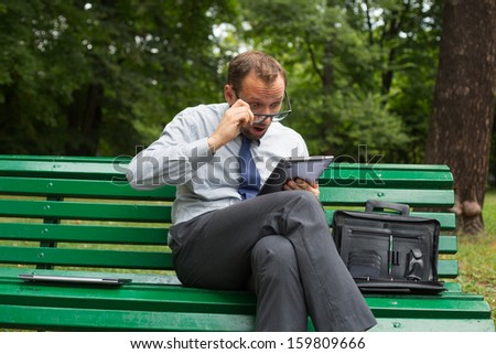 Businessman sitting on a bench with tablet pc. He is full of negative emotion.