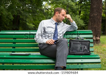 Businessman sitting on a bench with tablet pc. He is full of negative emotion. - stock photo