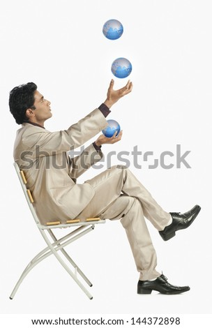 Businessman sitting on a chair and juggling with globes - stock photo