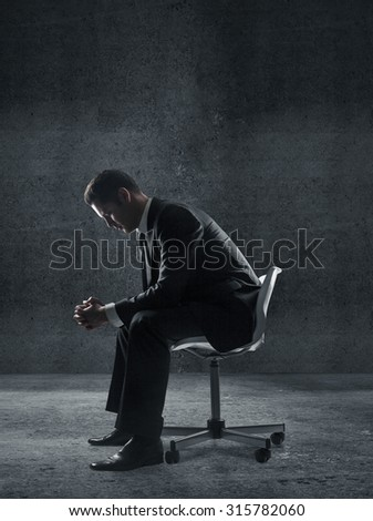 businessman sitting on a chair in dark room - stock photo