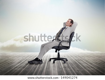 Businessman sitting on a chair over wooden boards on blue sky background - stock photo
