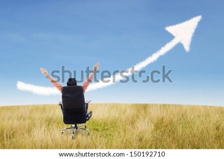 Businessman sitting on a chair with raised arms and up arrow sign cloud on wheat field - stock photo