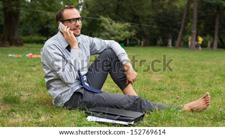 Businessman sitting on a grass and chatting on a cell phone with a happy expression.