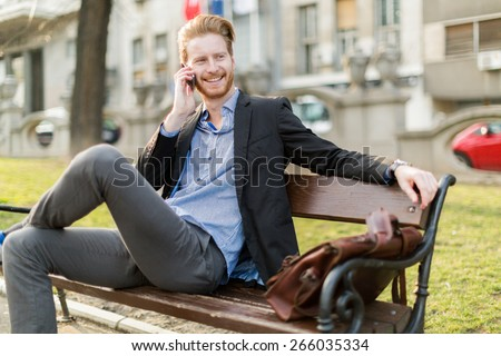 Businessman sitting on a park  bench while talking on the phone on a sunny day and happily smiles - stock photo
