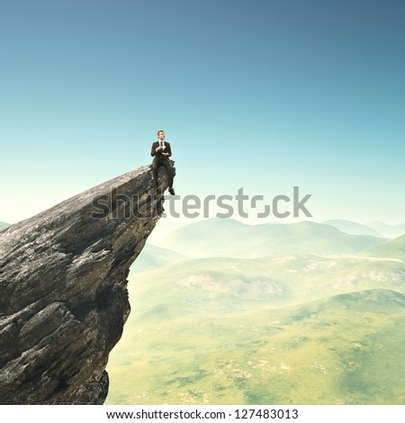 Businessman sitting on a peak with cup of coffee