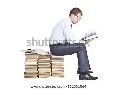 Businessman sitting on a stack of books and reading opened big book