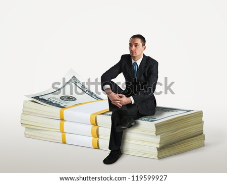 Businessman sitting on a stack of dollars
