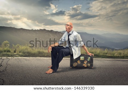 businessman sitting on a suitcase in the middle of the road destroyed by the heat - stock photo