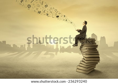 Businessman sitting on books and send information with laptop computer through sky - stock photo