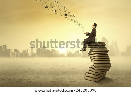 Businessman sitting on books and using laptop computer to send message - stock photo