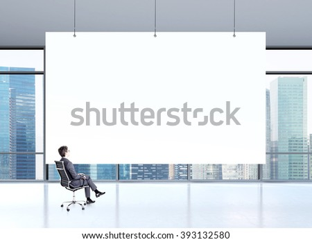 Businessman sitting on chair, big white poster in front. Panoramic window with Singapore view at background. Concept of planning. - stock photo