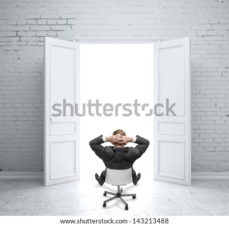 businessman sitting on chair in brick room - stock photo